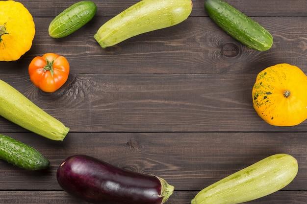 Pomodoro, cetrioli, zucche del cespuglio, melanzane e zucchine sulla tavola di legno scura con il fondo del copyspace