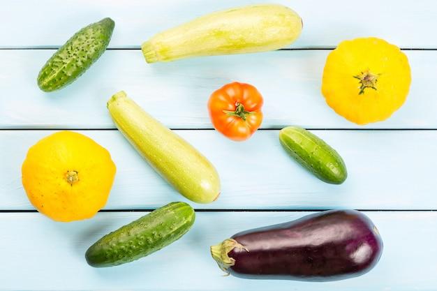 Pomodoro, cetrioli, zucche di cespuglio, melanzane e zucchine sul tavolo di legno blu,