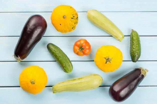 Pomodoro, cetrioli, zucche di cespuglio, melanzane e zucchine sul tavolo di legno blu.