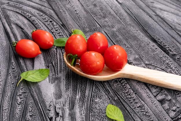 Pomodoro ciliegia in cucchiaio di legno altri pomodori e foglie su struttura di legno