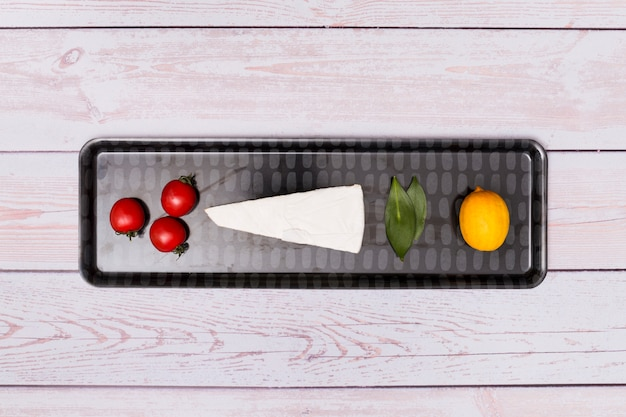 Pomodoro ciliegino; formaggio; foglie di alloro e limone sul vassoio nero sulla superficie in legno