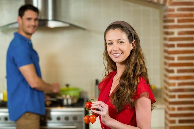 Pomodoro di ciliegia della tenuta della donna ed uomo che cucinano sulla stufa in cucina a casa