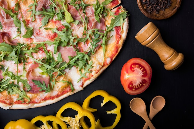 Pomodoro dimezzato; fette di peperone giallo; cucchiaio di legno e peppermill vicino deliziosa pizza italiana
