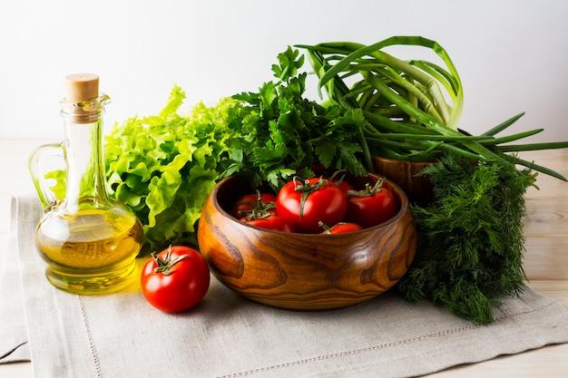 Pomodoro fresco in ciotola di legno e olio d'oliva