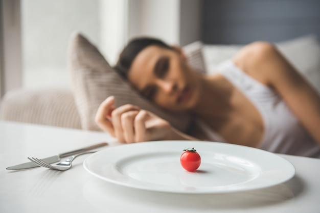 Pomodoro piccolo sul piatto in primo piano.