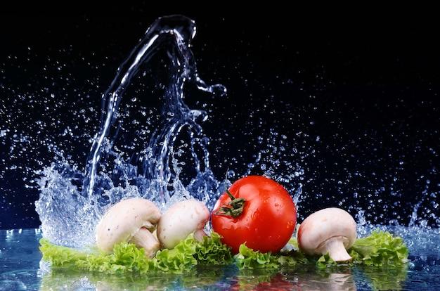 Pomodoro rosso ciliegia, funghi e insalata verde fresca con acqua goccia splash