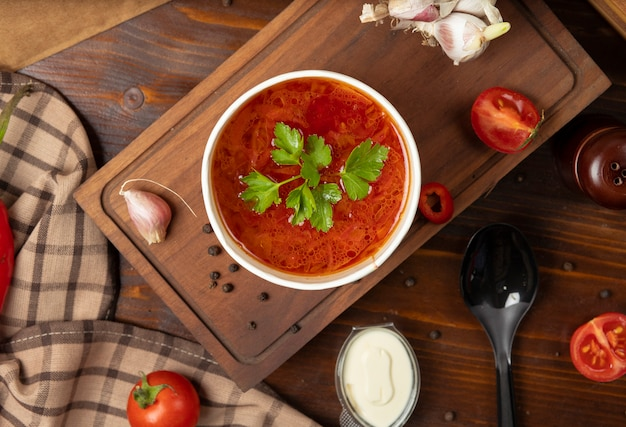 Pomodoro rosso, zuppa di verdure borsh in tazza usa e getta servita con verdure verdi