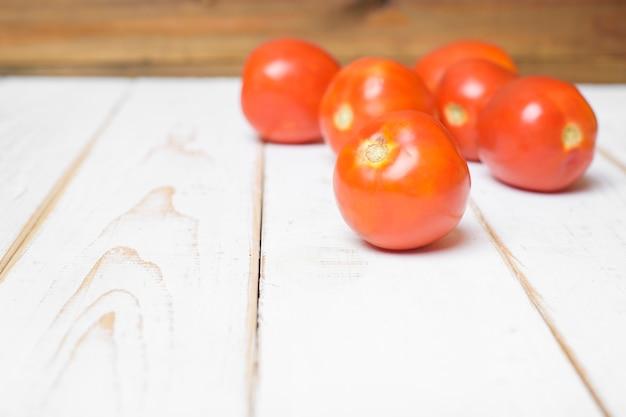 Pomodoro su fondo di legno bianco.