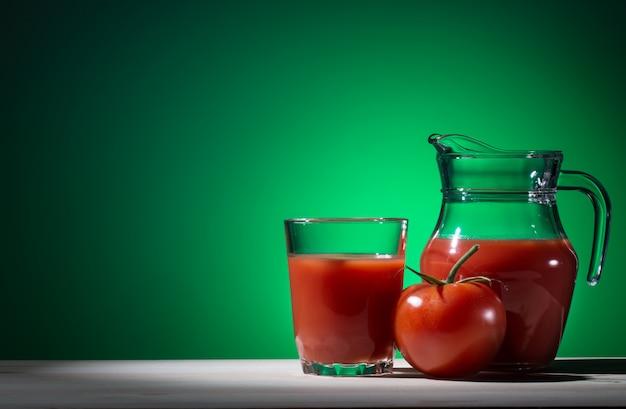 Pomodoro, vetro e brocca di succo di pomodoro su verde