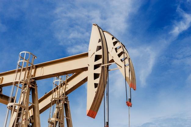 Pompa dell'olio in movimento. attrezzatura di industria petrolifera con cielo blu