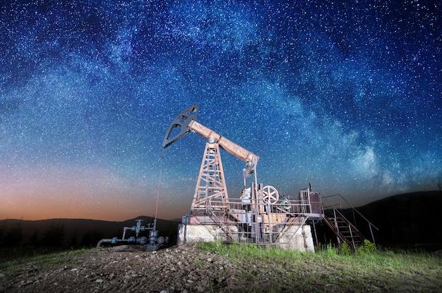 Pompa dell'olio sul giacimento di petrolio nella notte