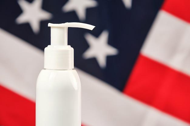 Pompa per alcol disinfettante per mani bianca senza etichetta per lavaggi frequenti e disinfezione delle mani sulla parete della bandiera degli stati uniti.