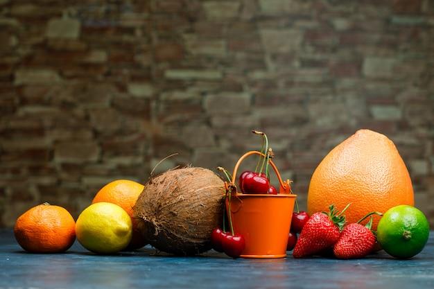 Pompelmo con arancia, lime, limone, fragola, ciliegia, mandarino, cocco vista laterale su pietra di mattoni e sfondo blu