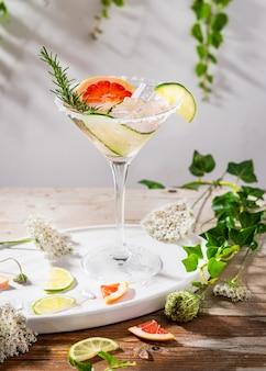 Pompelmo e cetriolo, rosmarino e lime cocktail, bevande rinfrescanti e fredde con ghiaccio su un tavolo rustico.