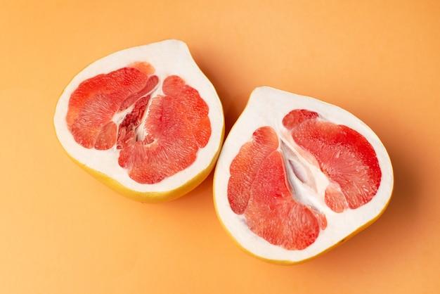 Pompelmo fresco su una superficie arancione, primo piano. concetto di sesso. il concetto di salute delle donne.