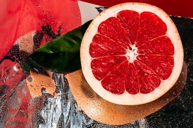Pompelmo rosso fresco sulla superficie dello specchio di riflessione