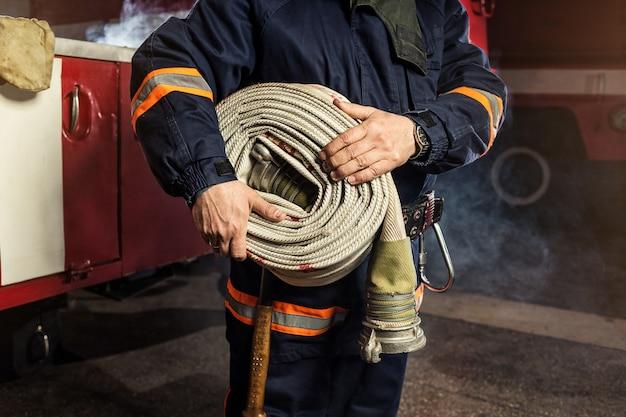 Pompiere (pompiere) in azione con una manichetta antincendio arrotolata vicino a un camion dei pompieri. sicurezza di emergenza. protezione, salvataggio dal pericolo.