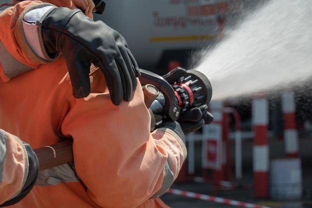 Pompieri che si preparano con il tubo flessibile dell'acqua