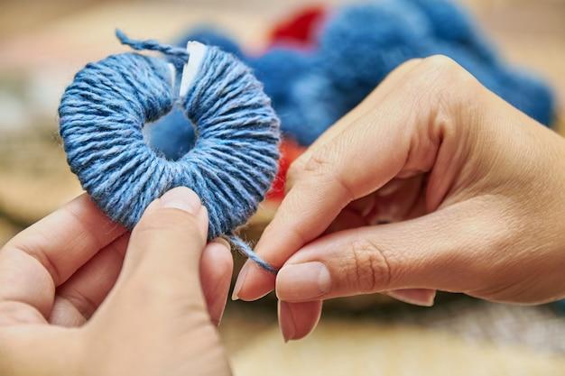 Pompon fatti a mano. il processo di creazione dei pompon dai fili della donna