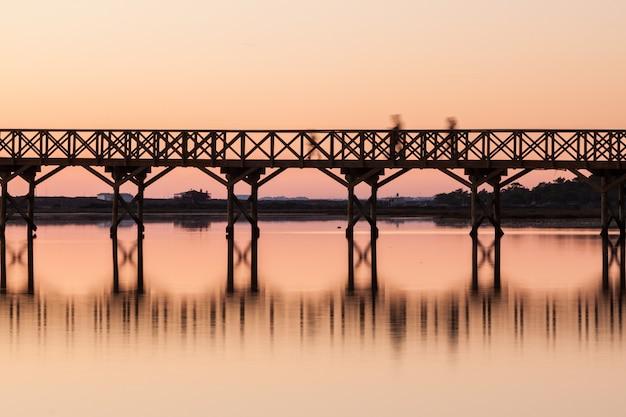 Ponte di legno al tramonto con sagome di persone. quinta de lago