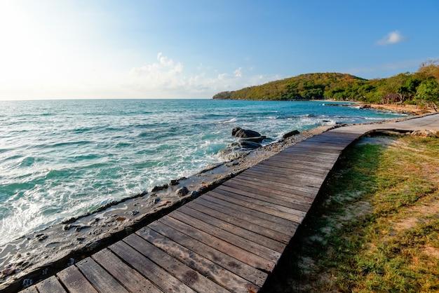 Ponte di legno balcone vista paesaggio marino idilliaco sagoma del mare albero tropicale spiaggia vacanze estive - terrazza vista mare con tavolo in legno vuoto sulla spiaggia paesaggio natura con luce solare alba