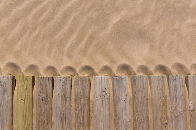 Ponte di legno di pino esposto alle intemperie nella struttura della sabbia della spiaggia