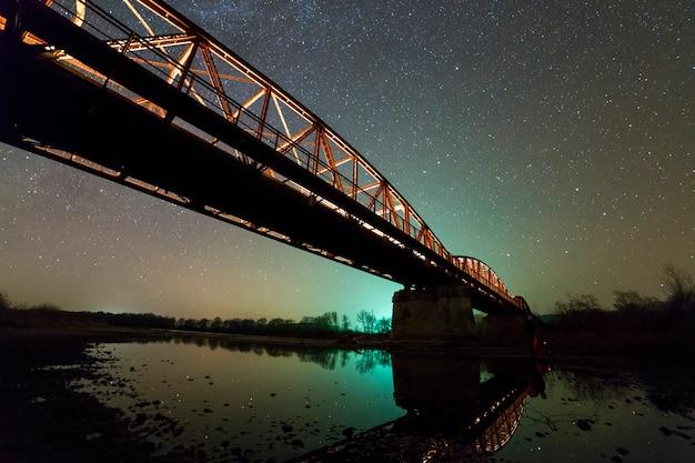 Ponte di metallo illuminato su supporti in cemento riflesso nell'acqua sul cielo stellato scuro con costellazione della via lattea. concetto di fotografia notturna.