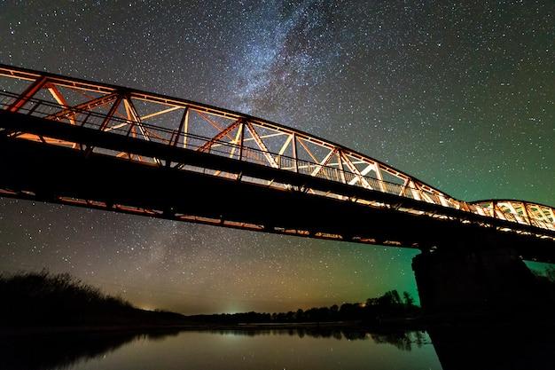 Ponte di metallo illuminato su supporti in cemento riflesso nell'acqua sul cielo stellato scuro con sfondo della costellazione della via lattea. concetto di fotografia notturna.