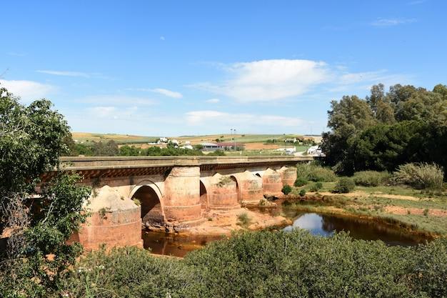 Ponte romano e rio tinto nel villaggio di niebla, provincia di huelva, andalusia, spagna
