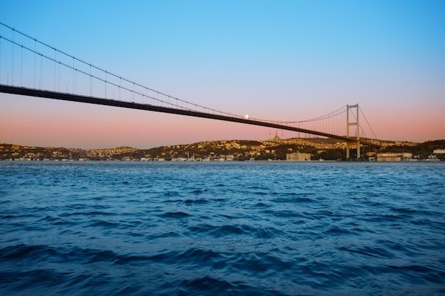Ponte sul bosforo all'alba crepuscolare sotto la luna luminosa