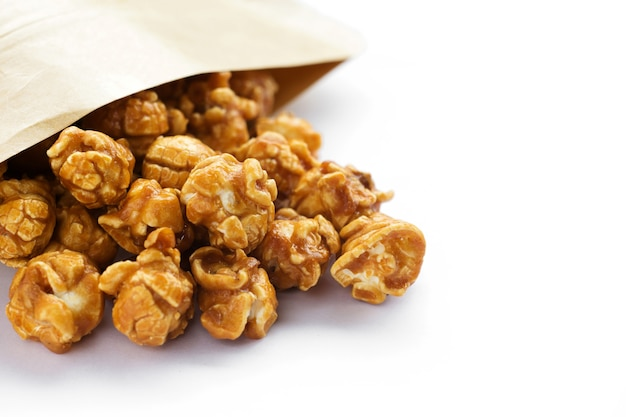 Popcorn al caramello su sfondo bianco.