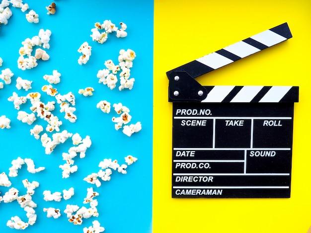 Popcorn, bicchieri per cinema e ciak su sfondo colorato.
