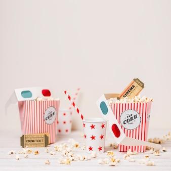 Popcorn; biglietto del cinema; vetro usa e getta con cannuccia e scatola di popcorn sul tavolo su sfondo bianco