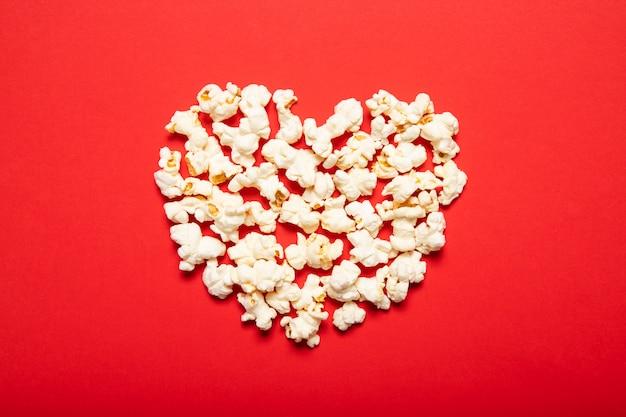 Popcorn delizioso su uno sfondo rosso. vista dall'alto, posto per il testo.