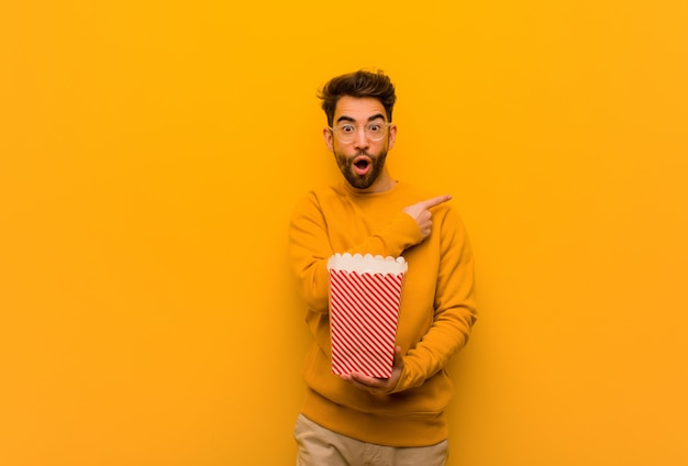 Popcorn della tenuta del giovane che indicano il lato con il dito