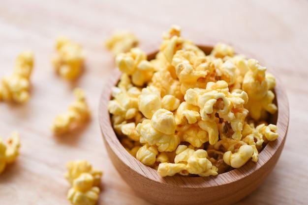 Popcorn dolce del burro in ciotola su di legno