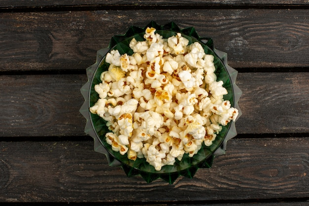 Popcorn fresco una vista dall'alto all'interno del piatto rotondo su un marrone