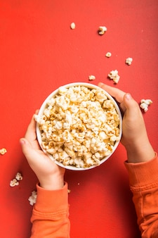 Popcorn fresco versato dalla ciotola sul rosso
