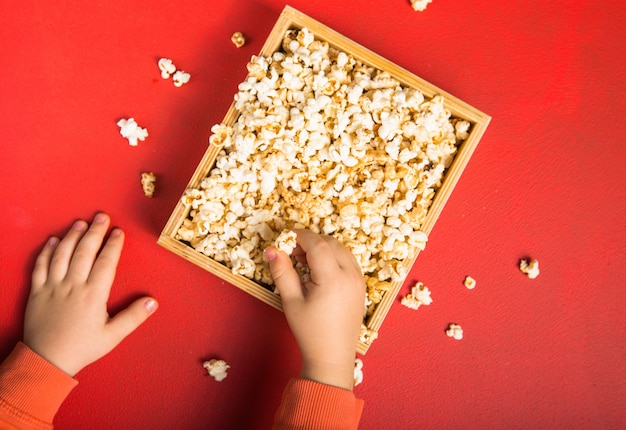Popcorn fresco versato fuori dalla scatola sul rosso