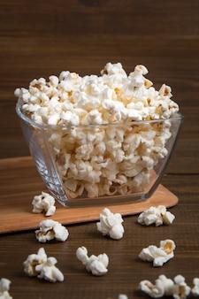 Popcorn in ciotola di vetro su legno