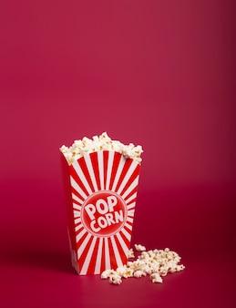 Popcorn in secchio a strisce su sfondo rosso. mais caldo sparso dalla scatola di carta, spazio della copia. fast food e snack cinematografici.
