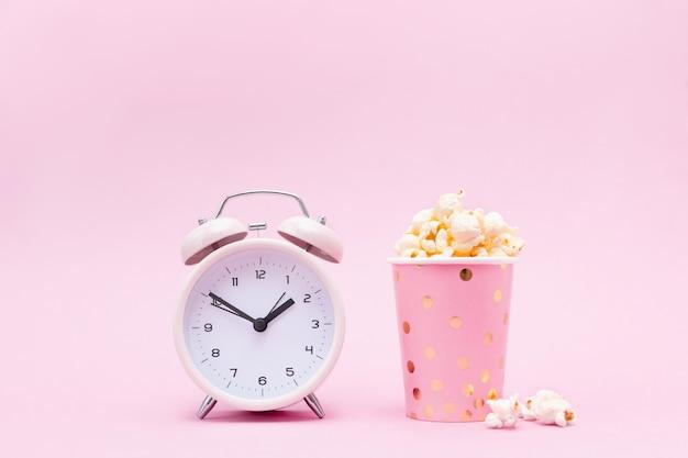 Popcorn in un vetro luminoso e sveglia sul rosa