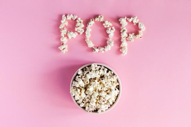 Popcorn in una ciotola rosa su fondo rosa, vista superiore