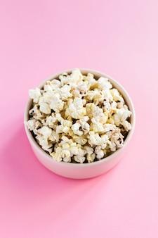 Popcorn in una ciotola rosa su sfondo rosa