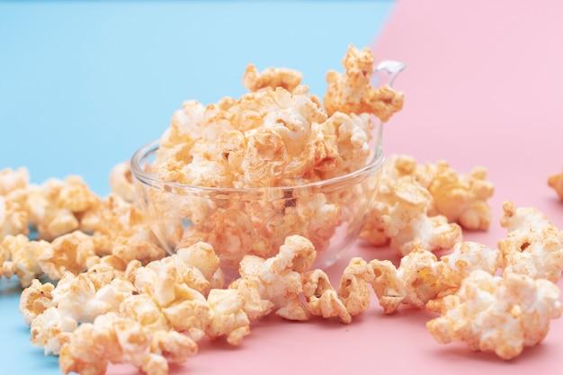 Popcorn in una ciotola su blu e rosa