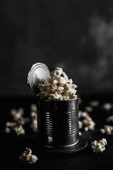 Popcorn in una latta d'acciaio su fondo scuro, popcorn tutt'intorno, foto lunatica