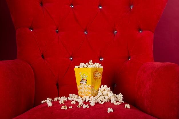 Popcorn isolato nel divano rosso