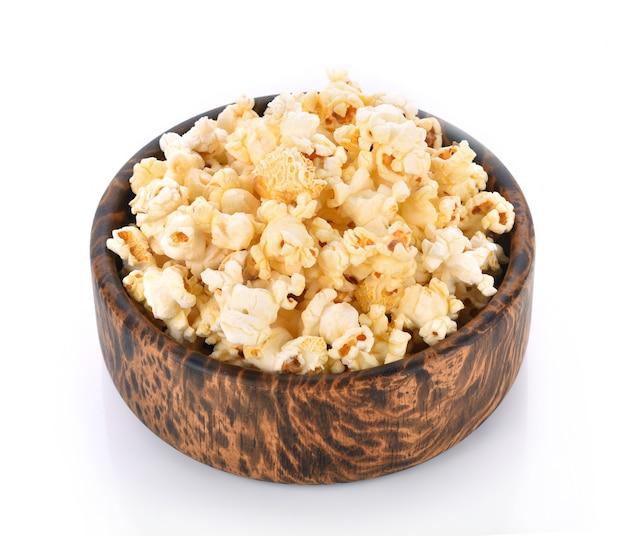 Popcorn nella ciotola di legno isolato su uno sfondo bianco