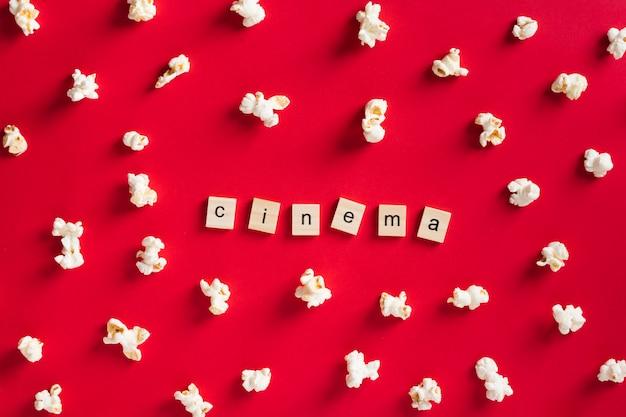 Popcorn piatto laici su sfondo rosso con scritte cinema