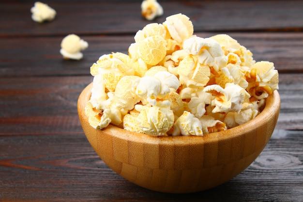 Popcorn salato in una ciotola di legno su un tavolo di legno.